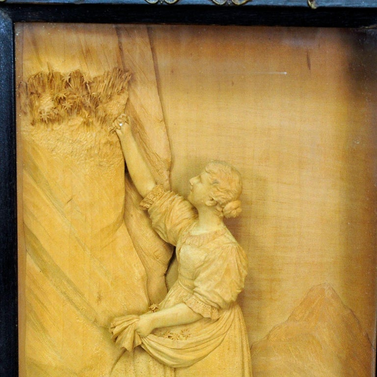 Item e4758 A tridimensional micro woodcarving of a folksy scenery. A young lady in traditional costume is picking edelweiss flowers in the mountains. Carved by the woodcarver ernst steiner (1864-1934), son of sebastian steiner, meran. With