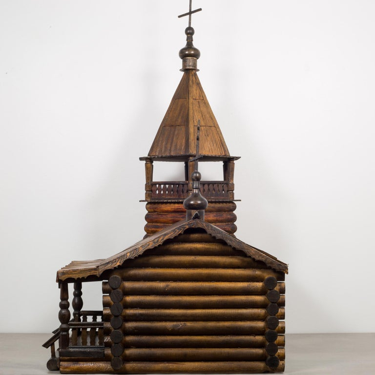This is an original wooden Russian Orthodox Church log cabin model. The log cabin lower section has two windows and a front porch with a highly carved front door that opens and closes. The porch has a highly detailed roof. The upper portion has a