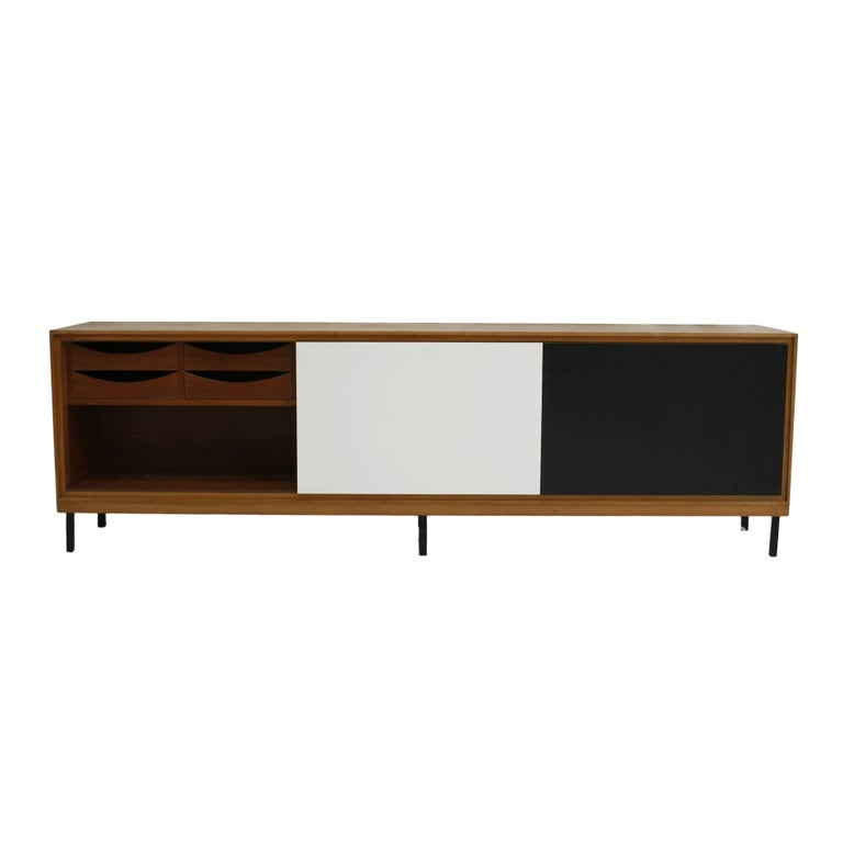 Solid teak wood sideboard with three sliding doors lacquered in color. Interior with drawers and formed by six metallic feet lacquered in black, France 50 years.