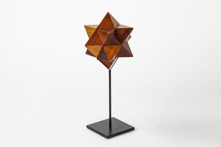 A sculptural wooden star form puzzle that is set an on a custom made stand. The puzzle can be taken off the stand to be appreciated and interacted with.