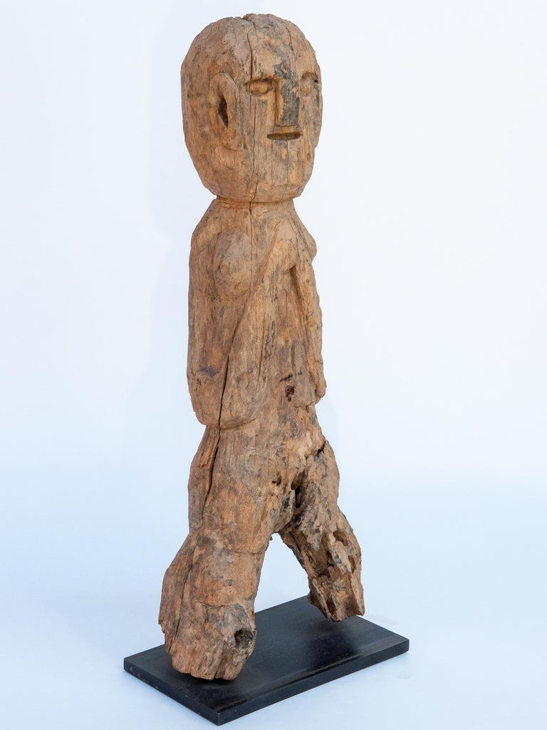 Wooden tribal female statue from West Nepal, early to mid-20th century. Mounted on a metal plate. Offered by Bruce Hughes. This wooden figure comes from West Nepal, most probably from the area of the Karnali river system. There is some mystery to