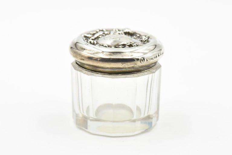Sterling silver and beveled crystal dresser jar from the Art Nouveau Era, made by fine American silver maker, Woodside. The jar is features a child hugging flowers on the side of a floral wreath. The jar measures 1.5