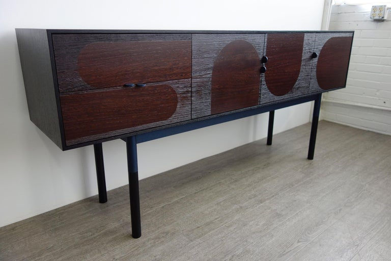 Sleek sideboard made of wengé, ebonized rift-sawn oak and steel. The doors are constructed of hand-sliced African wengé veneer and then media blasted to expose graphic arch patterns. The effect is stunning but subtle as the coarse texture reflects