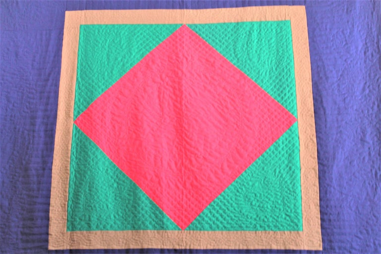This amazing all wool floating diamond in a square quilt is in fine condition and unusual colors. The centre diamond is in a cherry red with a large royal blue border. The quilting and piece work is the very best. This is a late but great quilt that