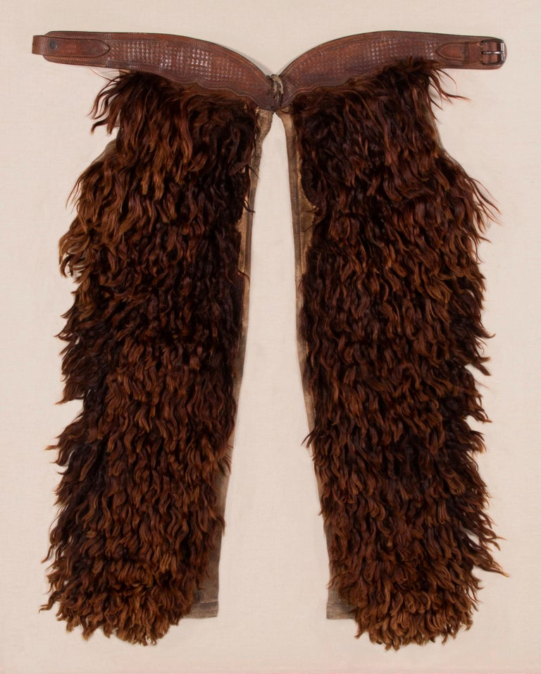 WOOLY, Angora chaps with beautifully tooled leather, made by the JOHN CLARK SADDLERY COMPANY OF PORTLAND, OREGON, SIGNED, CIRCA 1873-1929  Wooly chaps made of leather and canvas, faced with dyed Angora, made by the John F. Clark Saddlery Company