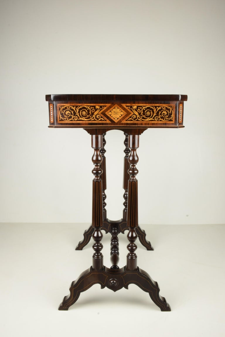 This table is characterized by the high quality of the decoration, a dense but orderly inlay, evident in the absolute precision in cutting and combination of the various materials (palisander, rosewood, boxwood and nacre), arranged on the bottom of