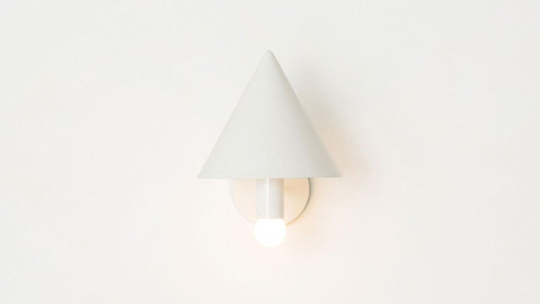 The canopy sconce deconstructs the conventional wall sconce into a series of expressed, geometric relationships. A bold conical shroud rises above a softly glowing bulb creating a canopy of diffused reflection. UL listed. Damp rated upon request.
