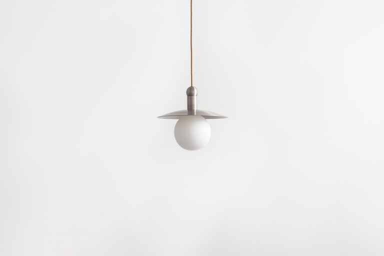 The Helios cord pendant positions a single glowing bulb against a stationary radiant dish, exploring the scale and illumination of an early American candle via the form of a traditional down-light pendant. With rotund details, each pendant provides