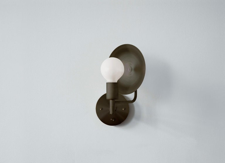 The Orbit sconce is a modern interpretation of an early American candle form with a reflective spun brass disc rotating 320 degrees, the sconce can act as both a reflector and deflector of light. The most elemental piece of the Orbit series, the