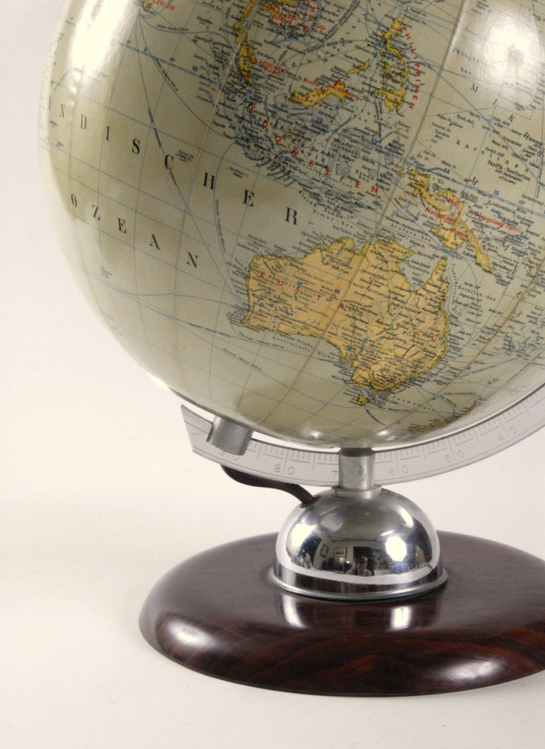 An excellent JRO made West Germany glass world globe light. Mounted on a Bakelite base with an aluminium gauge marked with latitude marks sitting on a chrome dome. The map paper is in excellent condition and when lit displays with a lovely soft warm
