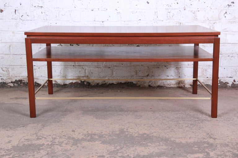 An exceptional Mid-Century Modern two-tier walnut and brass cocktail or coffee table designed by Edward Wormley for Dunbar Furniture. The table features gorgeous walnut wood grain and sleek, Minimalist mid-century design. Brass stretchers accent the