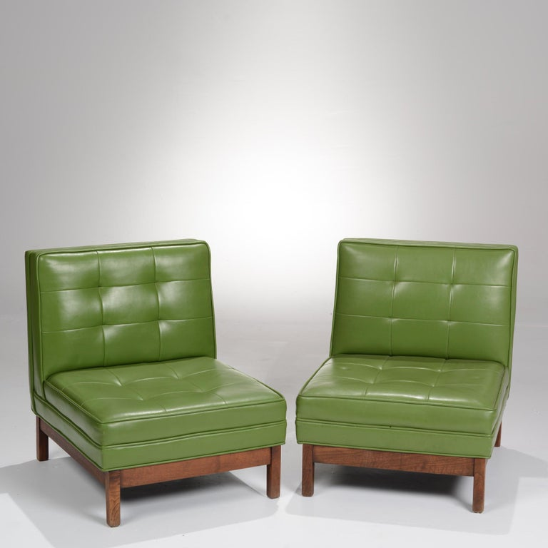 Pair of green vinyl and walnut slipper chairs in the style of Edward Wormley. These chairs are on display in our Los Angeles Arts District showroom, open 5 days a week.