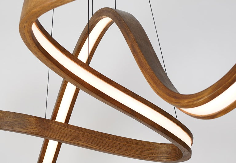 The woven is a independent modular freeform pendant formed from wood, woven diffuser, and high-output dimmable LED. The independent modular nature allows for a varying number of bent forms (two, three, four, etc.) to interwoven together but remain