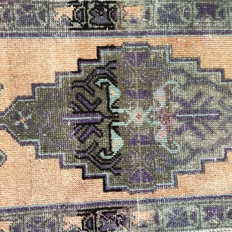 Peach and purple woven wool rug from Turkey. Featuring beautiful purple and peach tones and a geometric tribal pattern in the middle. Great for a hallway, beside a bed, in a foyer or kitchen.