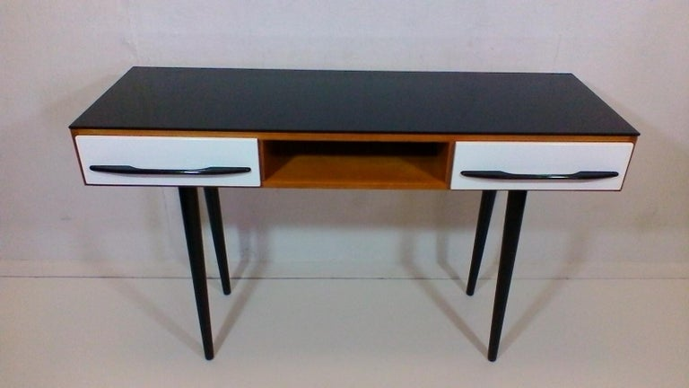 Czechoslovakia. The item is made of veneered and varnished wood, on upper surface is black opax glass, corpus is varnished quality polyurethane varnish. Drawers and legs are varnished into the original colors- black and white in high gloss. Complete