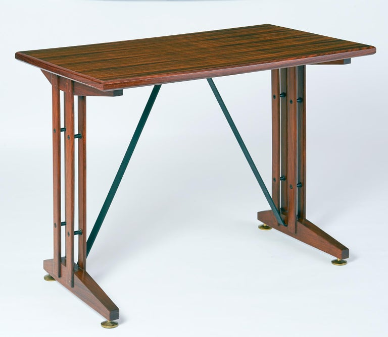 An elegant and compact writing or laptop  table, in polished wood with black iron stretchers and bronze adjusting feet. The perfect setting for a laptop, Italy, 1950s Dimensions: 39 x 22 x 30 H.