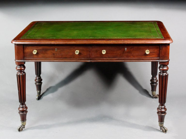 A small William IV mahogany writing on turned and reeded legs, 2 mahogany lined drawers with false drawers on the back and a fitted good quality green hide  Measures: Knee height 23.75