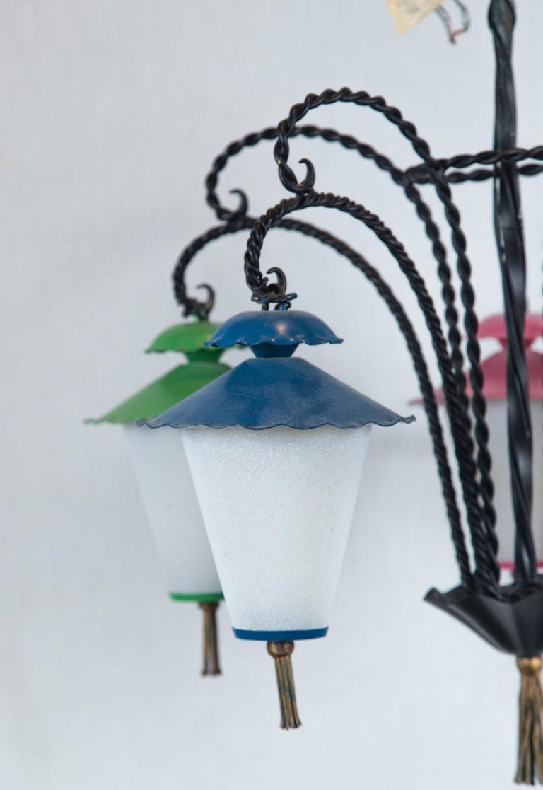 Wrought iron chandelier with five hanging Japanese style lanterns. Lanterns are milk glass with metal tops and metal bottoms embellished with brass tassels. Each lantern is painted a different color.