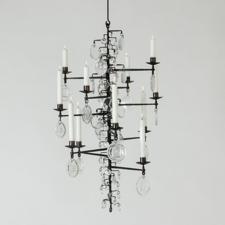 Stunning candle chandelier by Erik Höglund, made from wrought iron and glass. The long, rustic iron frame is adorned with different sized glass medallions that look like large rain drops on a bare tree. The biggest medallions are embossed with