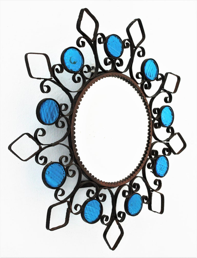 Beautiful hand-hammered iron sunburst mirror accented by blue glass circles, Spain, 1950s. This backlit wall mirror features a wrought iron frame with scrolled details, rhombus and circles adorned by small pieces of textured blue glass. It can be