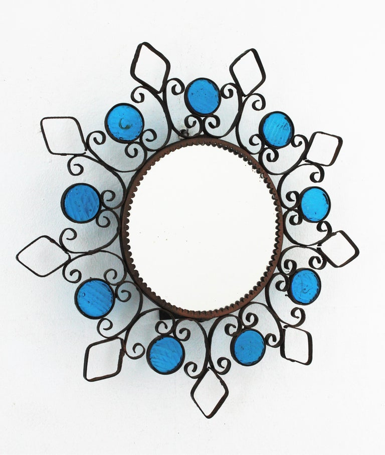 Mid-Century Modern Wrought Iron Backlit Sunburst Mirror with Blue Glasses and Scroll Motif For Sale