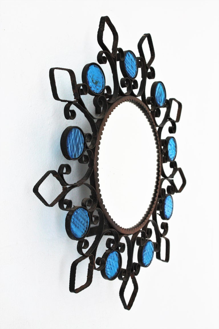 Spanish Wrought Iron Backlit Sunburst Mirror with Blue Glasses and Scroll Motif For Sale