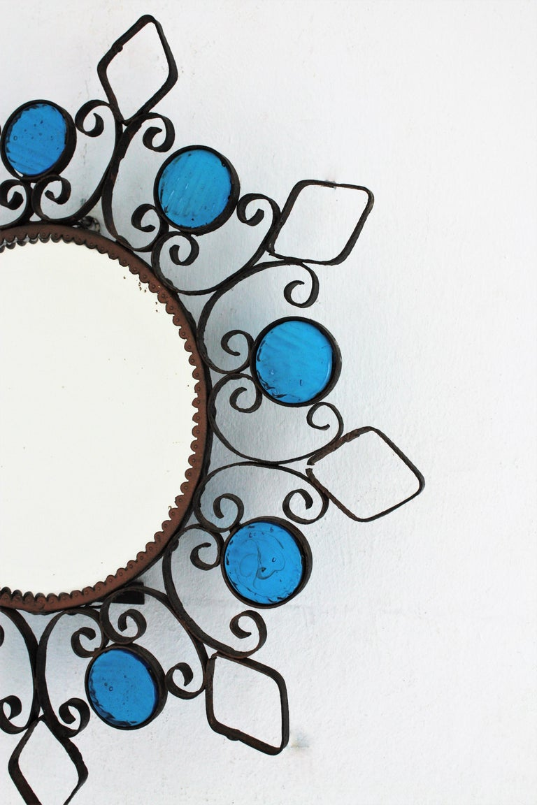 20th Century Wrought Iron Backlit Sunburst Mirror with Blue Glasses and Scroll Motif For Sale