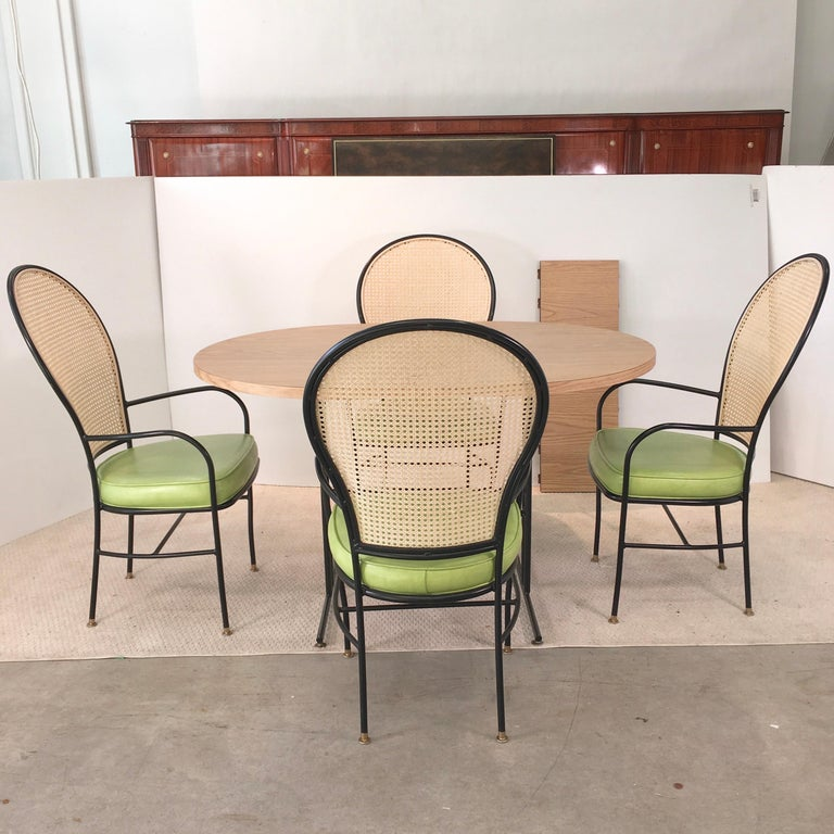 Vintage dinette with great silhouette in style of Tommi Parzinger. Four newly re-caned balloon back blackened iron arm chairs with lime green naugahyde seat cushions and brass tone glide feet. Racetrack oval light oak woodgrain laminate table,