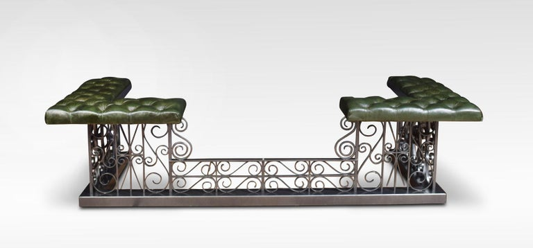 Wrought iron club fender, the deep buttoned leather upholstered padded seats, on square section supports with scrolling decoration. All raised up on plinth base.