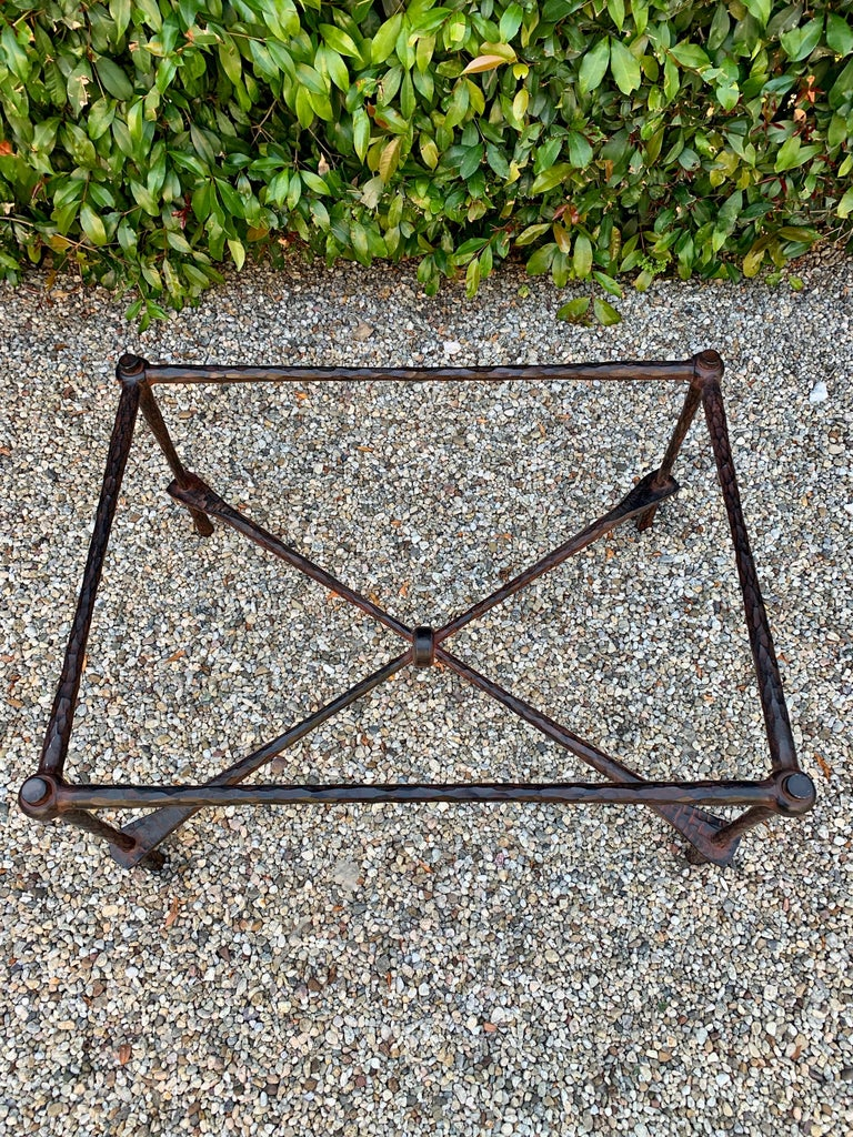 Wrought iron coffee table in the manner of Giacometti, a beautiful hammered wrought iron table. The finish on the iron has a reddish cast to the black iron, this could easily be changed. The piece is very well made and has a 1/2 inch glass top.