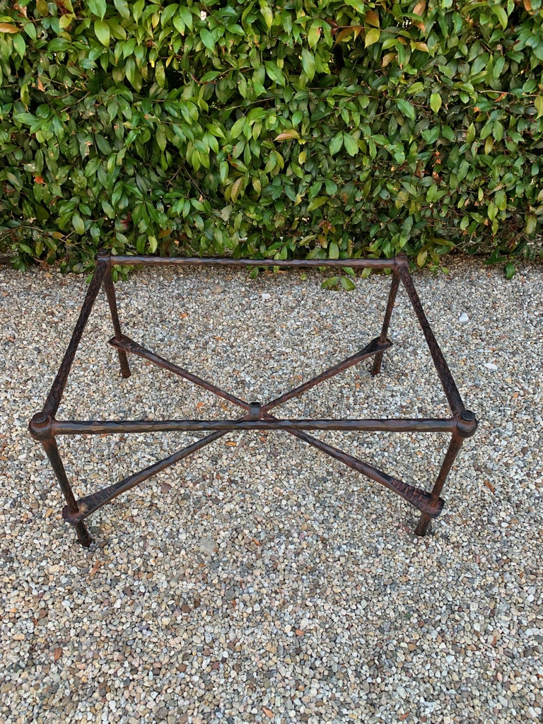 Wrought iron coffee table in the manner of Giacometti - a beautiful hammered wrought iron table. The finish on the iron has a reddish cast to the black iron, this could easily be changed. The piece is very well made and has a 1/2 inch glass top.