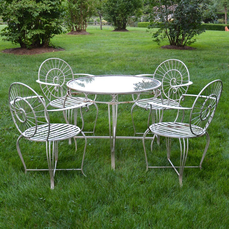 A wrought iron dining suite comprised of four armchairs, the chairs with slatted seats, cabriole legs, and the chair backs with stylized nautilus shell design, the round table with cabriole legs and stylized nautilus top, with inset glass. Measures: