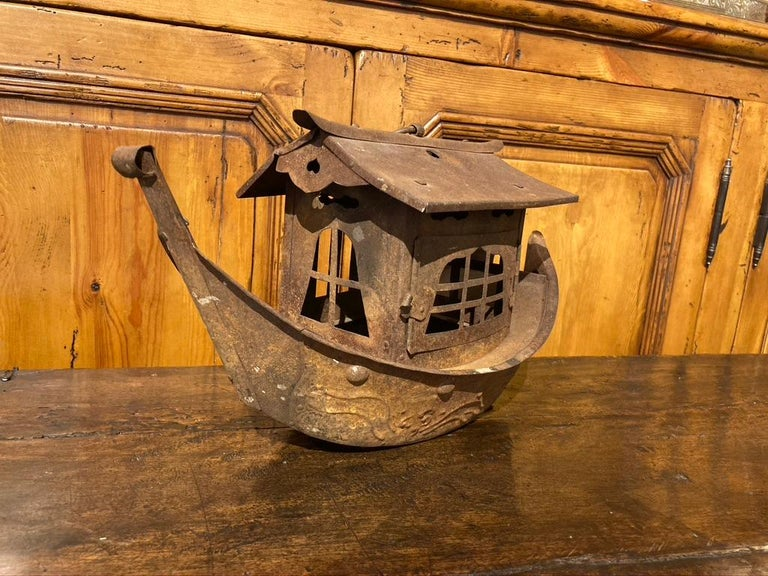 Charming and whimsical iron hanging lantern in the form of a the Chinese sailing vessels known as junks. The hull decorated with raised waves and round bosses, the cabin with a hinged door that opens so a candle can be placed inside. An iron ring on