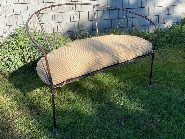 Wrought iron loveseat or settee is handcrafted. Great for indoor use and outdoor with treatment. Striped cushion custom made for seat. Lightly used. Slight rust color coming through in some spots. Iron slats seat like a basket weave