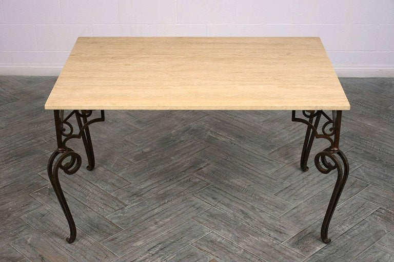 This 1970s Spanish style dining table features a wrought iron base and travertine top. The base is has scrolled legs with ornate buttress supports and a rustic finish. The travertine top is 3/4 inch thick with a rough edge. This dining table is