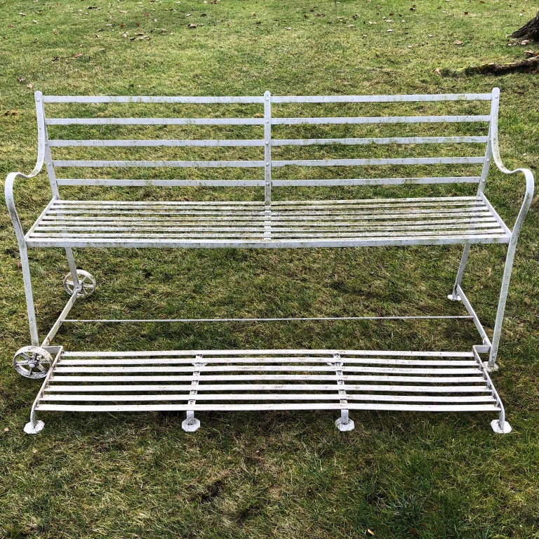 A rare Regency wrought iron games seat, the back with horizontal slats, with similar slatted seat and hinged footrest, on paw feet with wheels to one end. 39 ins. high, 76 ins. overall width, 35.5 ins. overall depth with footrest extended (24 ins.