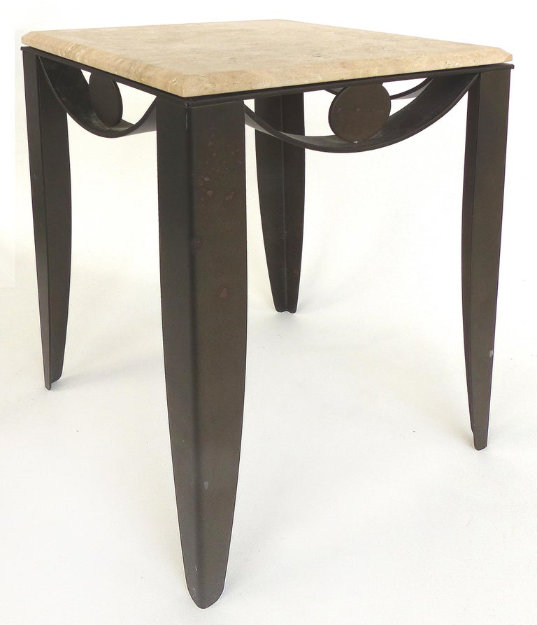 Offered for sale is a sculptural modern patinated wrought iron side table fitted with a beveled travertine stone top. The table has swagged iron side details that drape downward as legs.