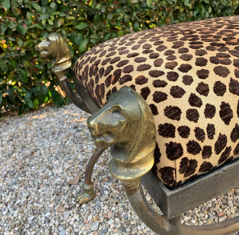 A wrought iron stool with cast brass lion head finials and paw feet. The shape and detailing are exceptional. A fabulous statement in newly upholstered cut velvet leopard, suiting any room, foot of the bed to library and guest room.  Seat is very
