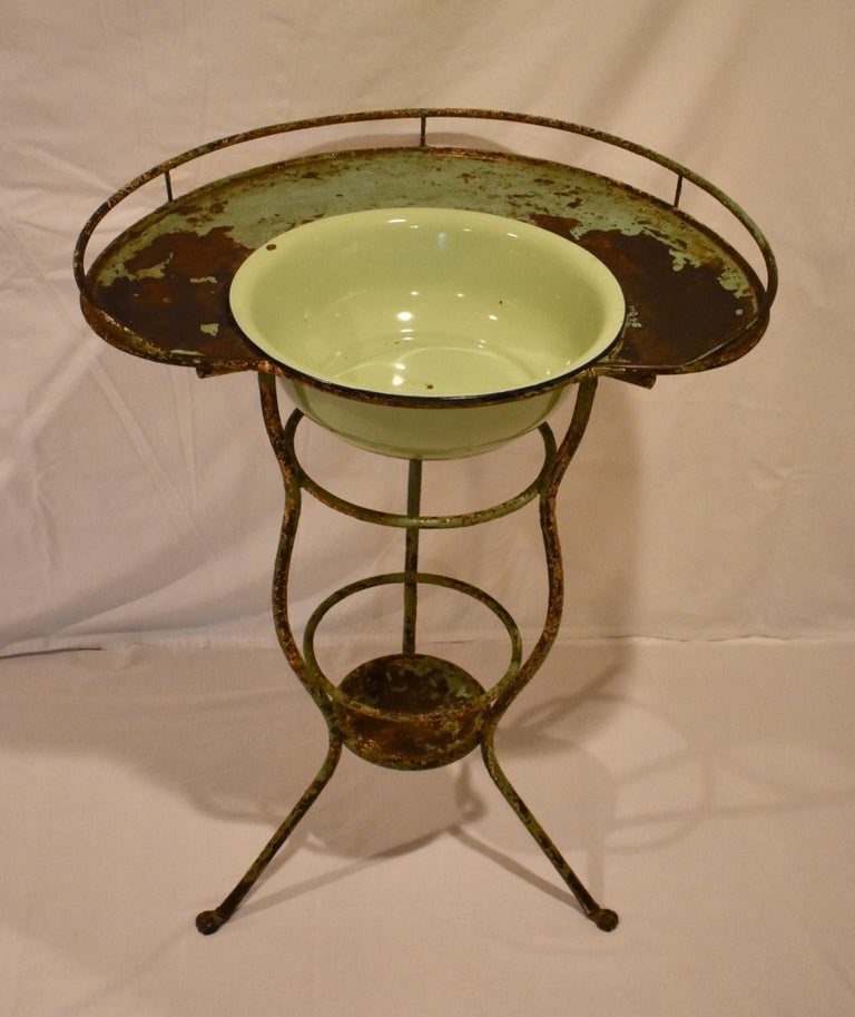 """This beautiful and rather unusual French curvilinear wrought iron washstand features a kidney-shaped surface with a beaded lip and gallery. This is supported by three serpentine legs ending in paw feet, joined by two iron rings and a lipped shelf 7"""""""