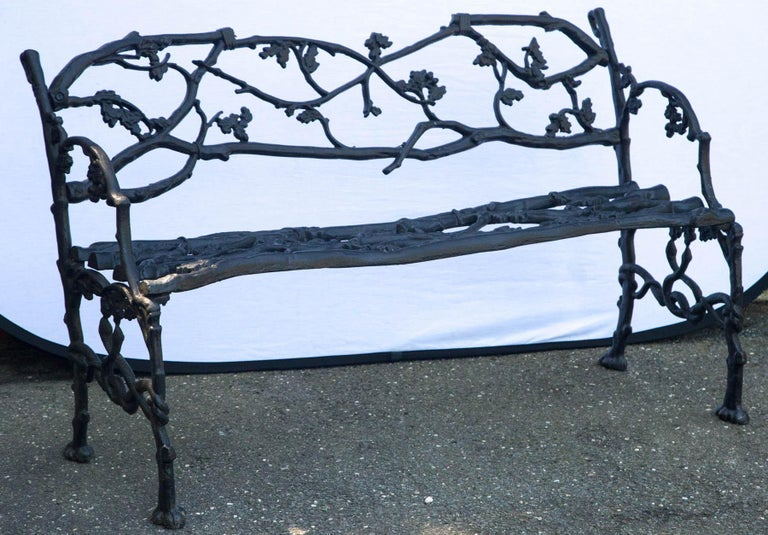 Wrought iron twig form bench having leaf decoration and intertwined snake stretcher.