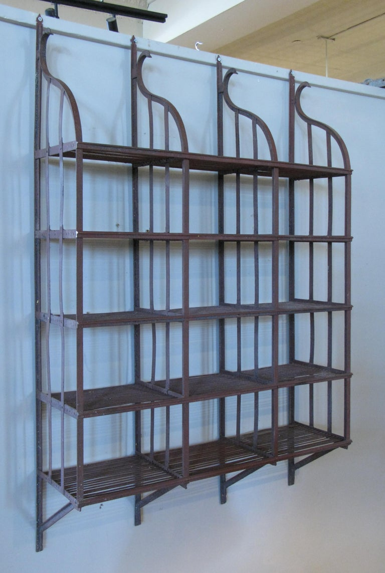 A beautiful vintage 1950s wrought iron wall-mounted hanging shelving rack, with curved top and five shelves. Perfect for kitchen, books, or plants.