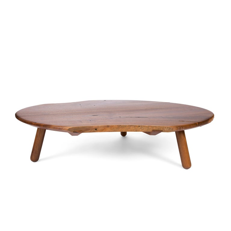 A handmade low table in walnut with a round form, natural edges when innate in the wood and three (3) substantial turned legs that are mortised through the top. The top consists of live edges, and solid boards joined together with sliding dovetail