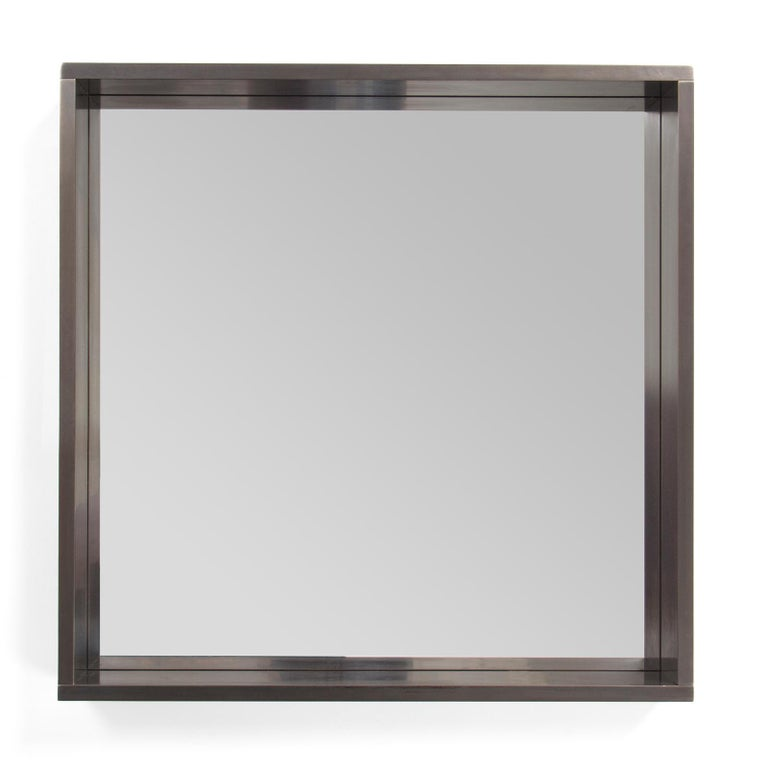 A square mirror with a dovetailed patinated steel frame.