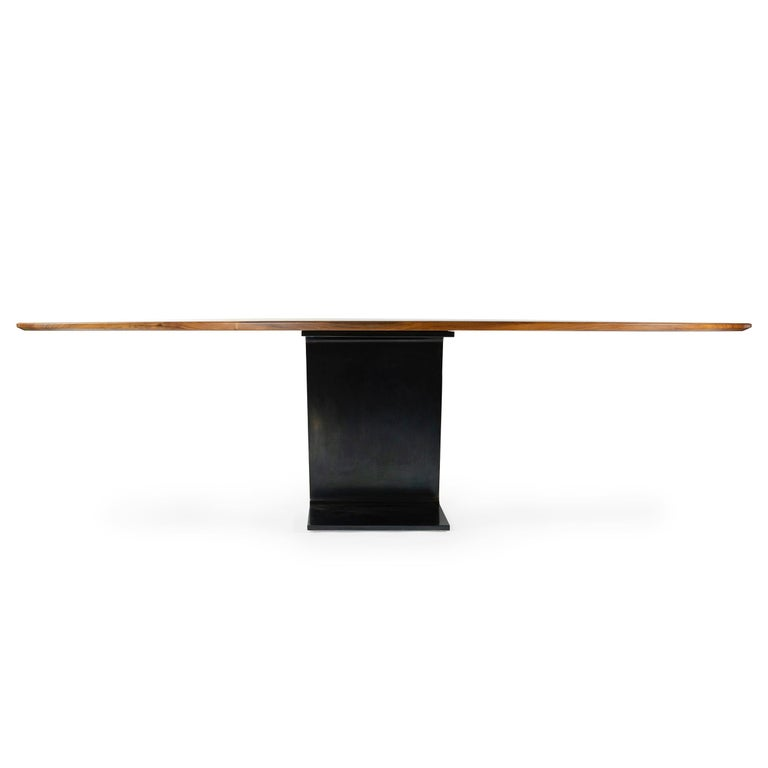 A custom ellipse table with a solid walnut wood top and patinated steel base. Wood top measures 53.75 x 108 inches. Manufactured in NY by the Wyeth Workshop. Available in custom sizes.