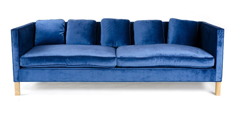A minimal tuxedo sofa with solid wood frame and hand tied springs having down-filled cushions and pillow backs upholstered in blue cotton velvet.