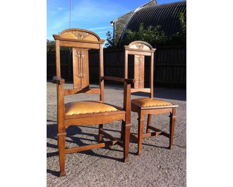Wylie and Lochhead. A set of four Arts & Crafts oak dining chairs consisting of two side chairs and two armchairs, with stylized Glasgow rose and floral carved details to the backs, in good solid condition. Professionally re upholstered in a quality