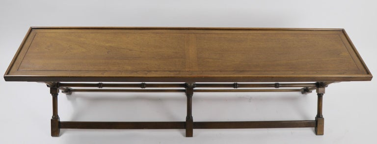 Architectural design coffee table by Brandt Furniture Company, circa 1960s-1970s. This stylish table is exceptionally long (62 inch ) it has three X-form legs, joined by turned wood stretchers, marked Brandt with original metal tag label on verso.