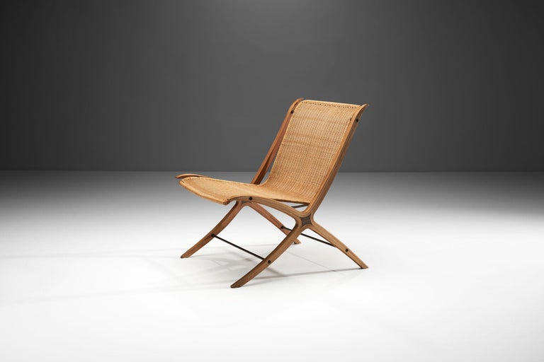 """This easy chair is the Danish designer duo's famous """"FH6135"""" model, commonly referred to as the """"X-Chair"""". The name derives from the distinctive X-shaped side frames of the chair. This detail contributes to the flowing, unbroken lines of the side"""