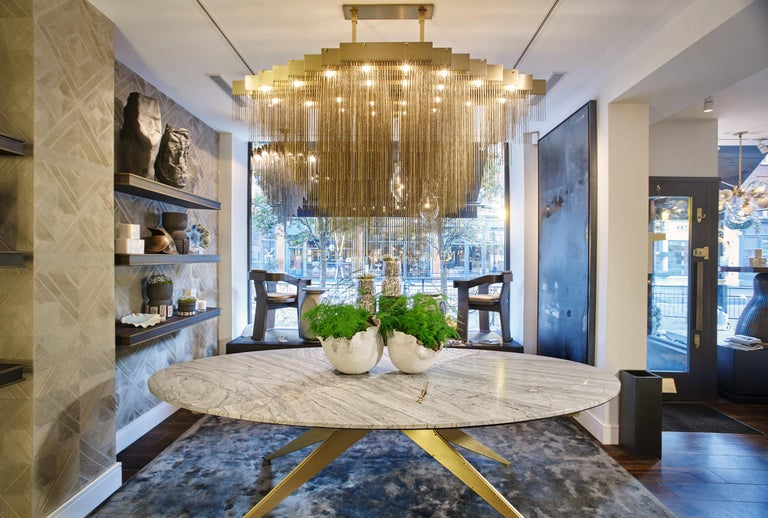 A chandelier that moves with glamorous intrigue, the Kelly chandelier's metallic chain cascades through its various layers to create a glisten reflective effect. A bold synergy of cold metal with warm light, the black or brass frame hosts a matching