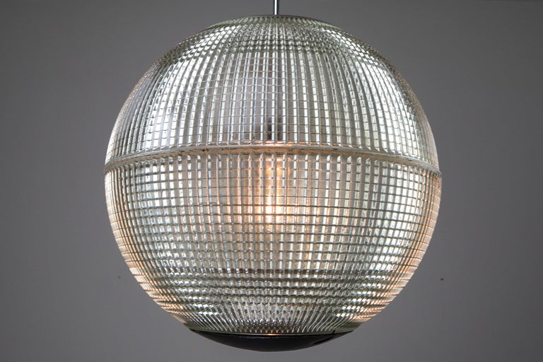 This is a large original late 1960s Paris globe Holophane Street light from Paris, France now turned into a pendant light. The hallmark of Holophane luminaries, or lighting fixtures, is the borosilicate glass reflector / refactor. The glass prisms